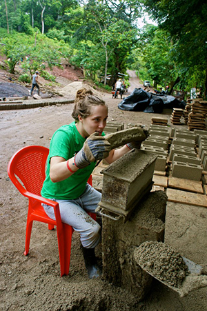 Young woman helping build a school