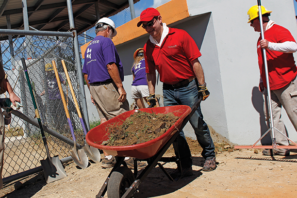 Volunteers work to restore a local baseball field.