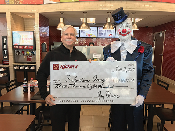 Dr. F. Duke Haddad standing with a clown holding a check for thirteen thousand eight hundred dollars to th Salvation Army