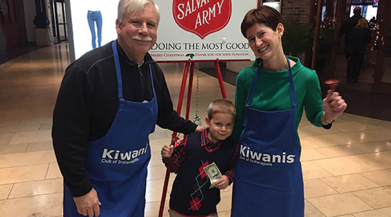 Dr. F. Duke Haddad and a woman in Kiwanis aprons at a Salvation Army donation location with a child donating money.