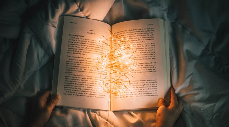 hands holding a book with lights in it