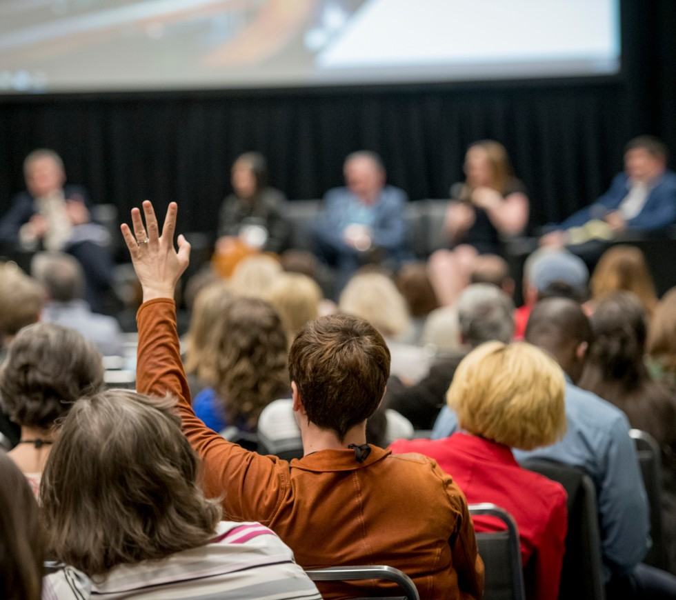 Man raising his hand to ask a question during a conference session