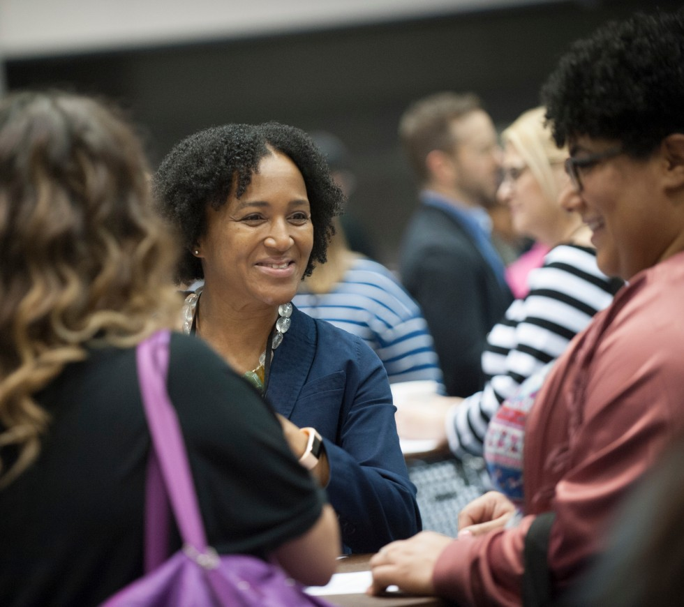 Woman smiling and networking with colleagues at an AFP conference