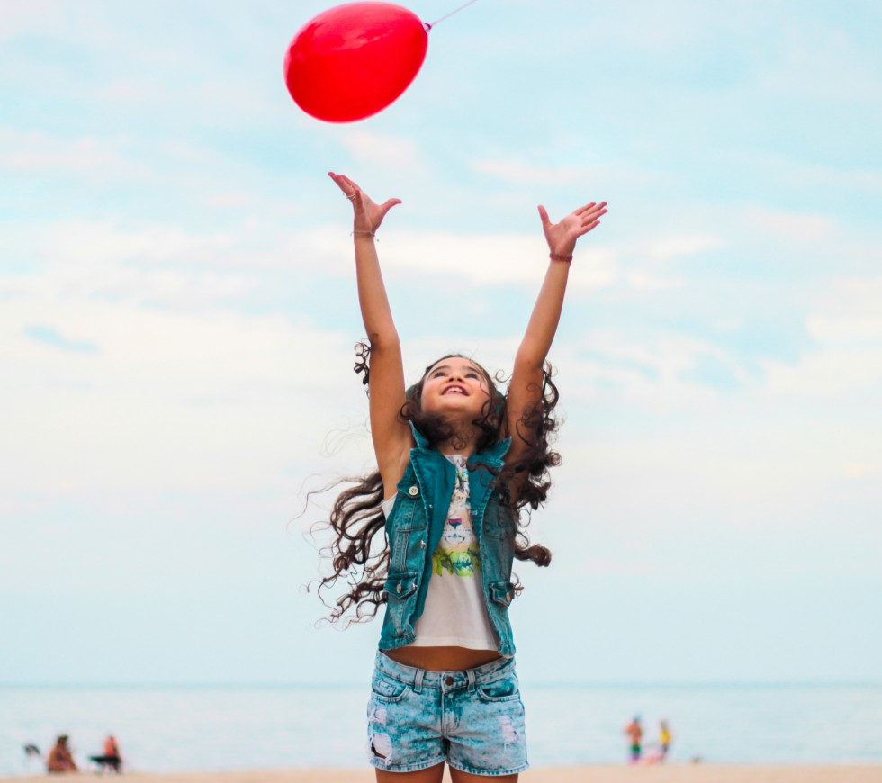 girl tossing a balloon