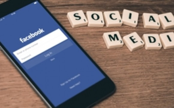 iphone showing facebook and scrabble tiles spell out social media