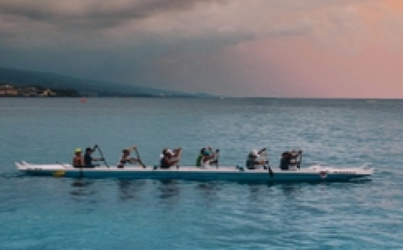 A team rowing a long canoe
