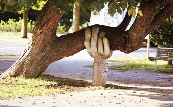 a large carved hand holding up a tree