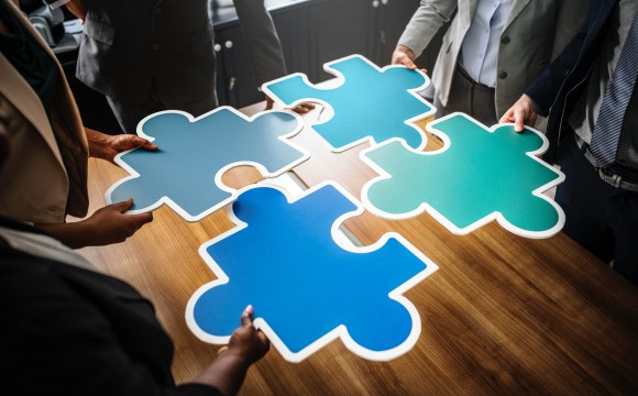 People putting a large jigsaw puzzle together