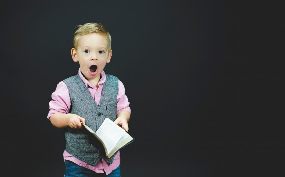 boy in pink shirt and grey vest reading a book and surprised