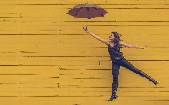 woman leaping with an umbrella in front of a yellow wall